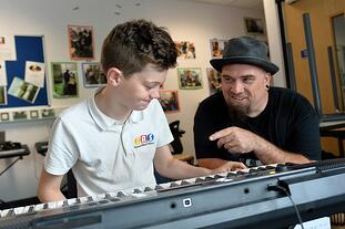 Boy playing keyboard to teacher