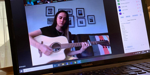 Student playing guitar online