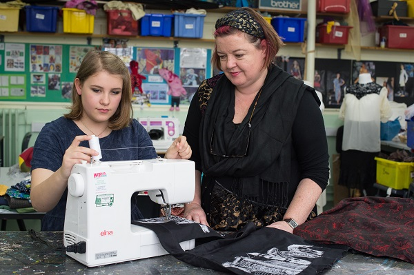 Girl being shown how to use a sewing machine
