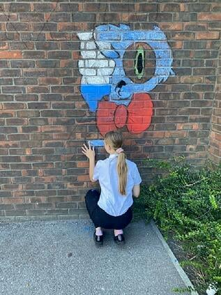 Girl drawing mural on brick wall using chalk