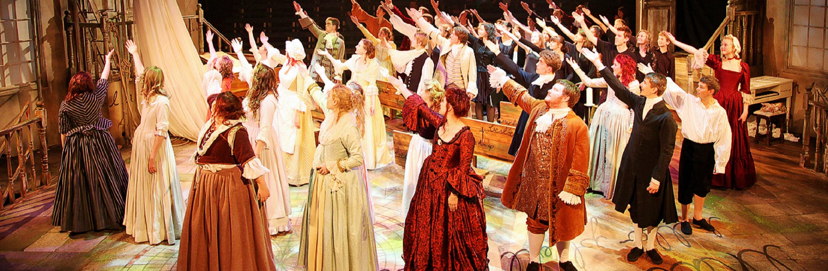Group of actors in Tudor period dress gesturing upwards